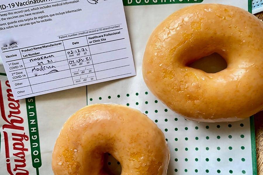 Krispy Kreme donuts next to COVID-19 vaccination card
